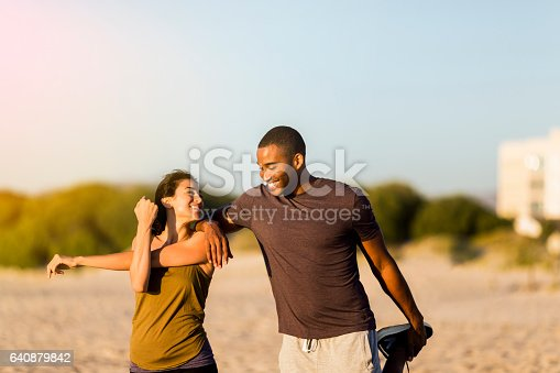 istock Happy couple doing stretching exercises at beach 640879842