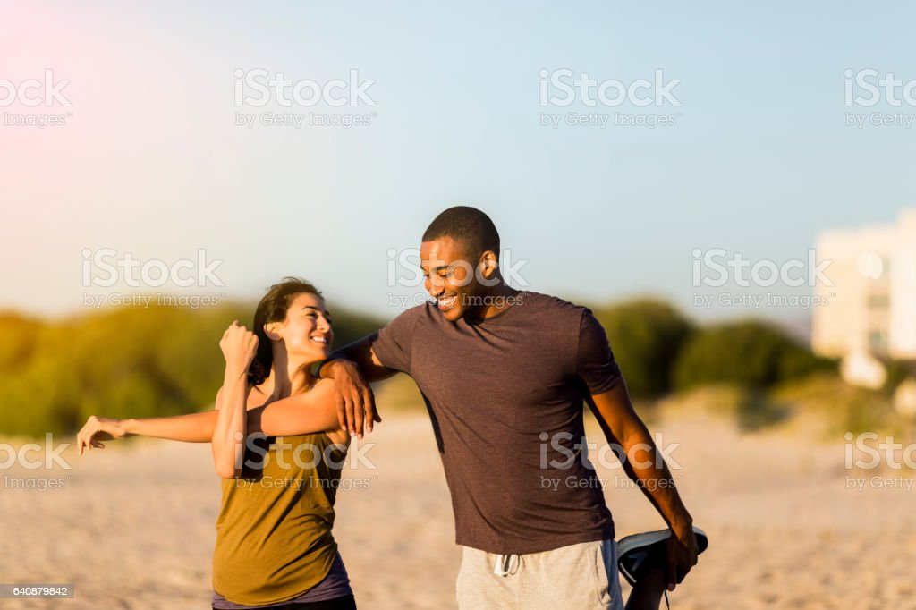 Happy couple doing stretching exercises at beach stock photo