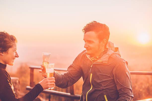 happy couple drinking beer after cross-country running, alps, autumn, europe - bier gesund stock-fotos und bilder