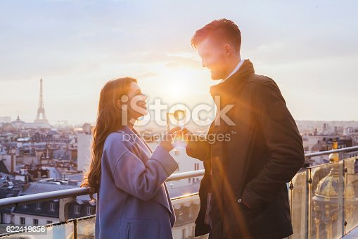 istock happy couple drinking champagne in Paris 622419656