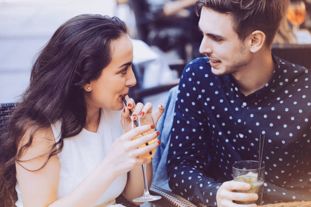 Happy couple drinking cocktails stock photo