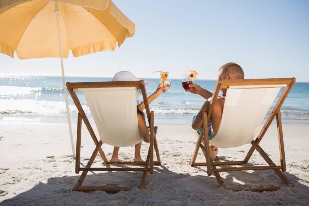glückliches paar cocktails trinken, während sie auf ihren liegestühlen entspannen - sonnenschirm terrasse stock-fotos und bilder