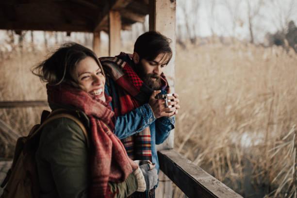 glückliches paar trinken heißen tee an einem kalten tag - mützenschal stock-fotos und bilder