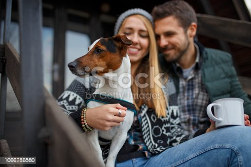 Happy couple drinking hot tea outdoor on cozy camping