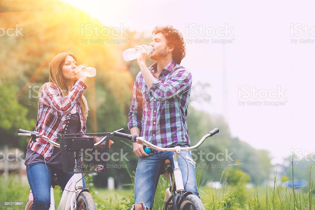 Feliz pareja bebiendo agua después de montar una bicicleta. - foto de stock