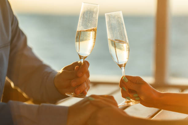 Happy couple drinks champagne on a yacht Glasses of wine in the hands of woman table for two stock pictures, royalty-free photos & images