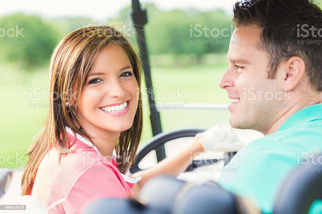 Happy couple driving golf cart while playing on green course stock photo