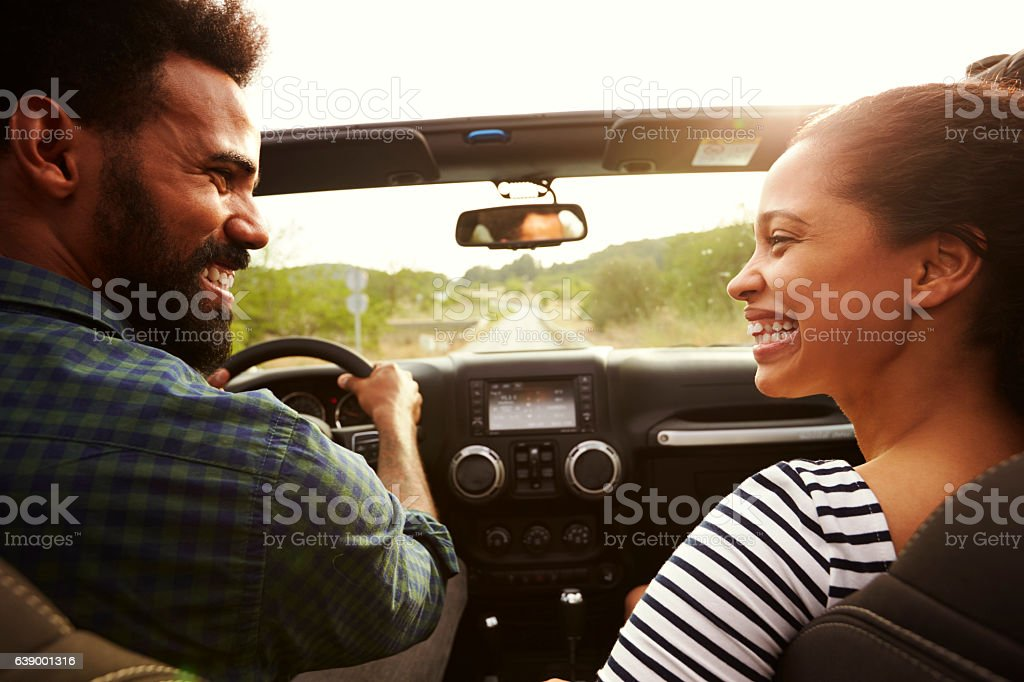 Happy couple driving in their car looking at each other stock photo