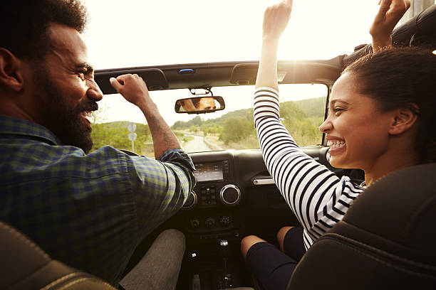 Happy couple driving in their car with arms in the air ストックフォト