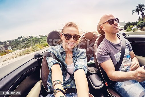 807410214istockphoto Happy couple driving open car and making selfie 1134232655