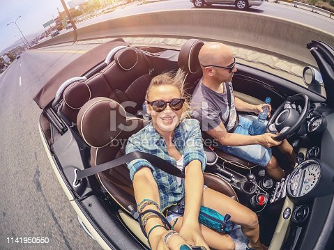 807410214istockphoto Happy couple driving open car and making selfie 1141950550