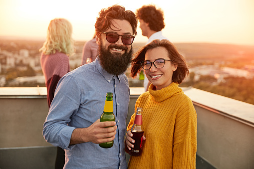 Cheerful man and woman with beer smiling and looking at camera while having fun with friends on rooftop during party