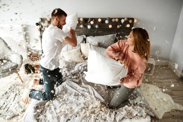 glückliches paar während kissen kämpfen unter gefieder fallen - lausbub tattoo stock-fotos und bilder