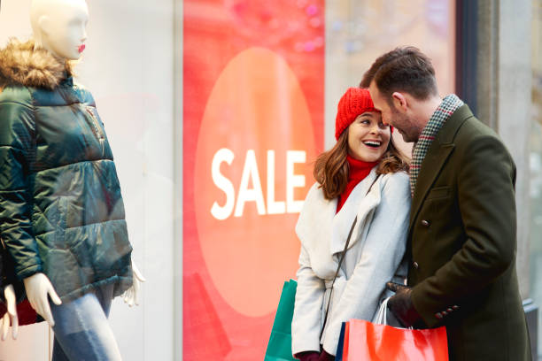 Happy couple during the window shopping in wintertime Happy couple during the window shopping in wintertime discount store stock pictures, royalty-free photos & images