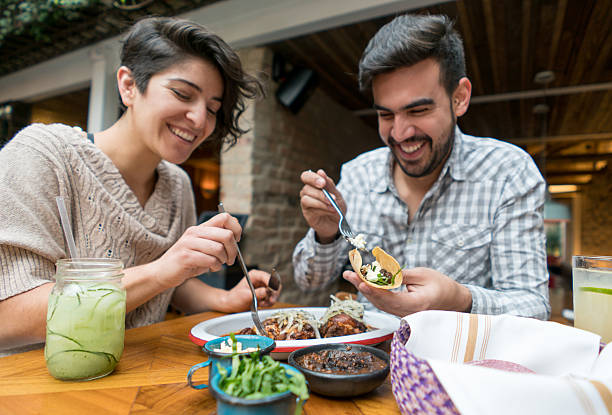happy couple eating at a restaurant - mexican food stock photos and pictures