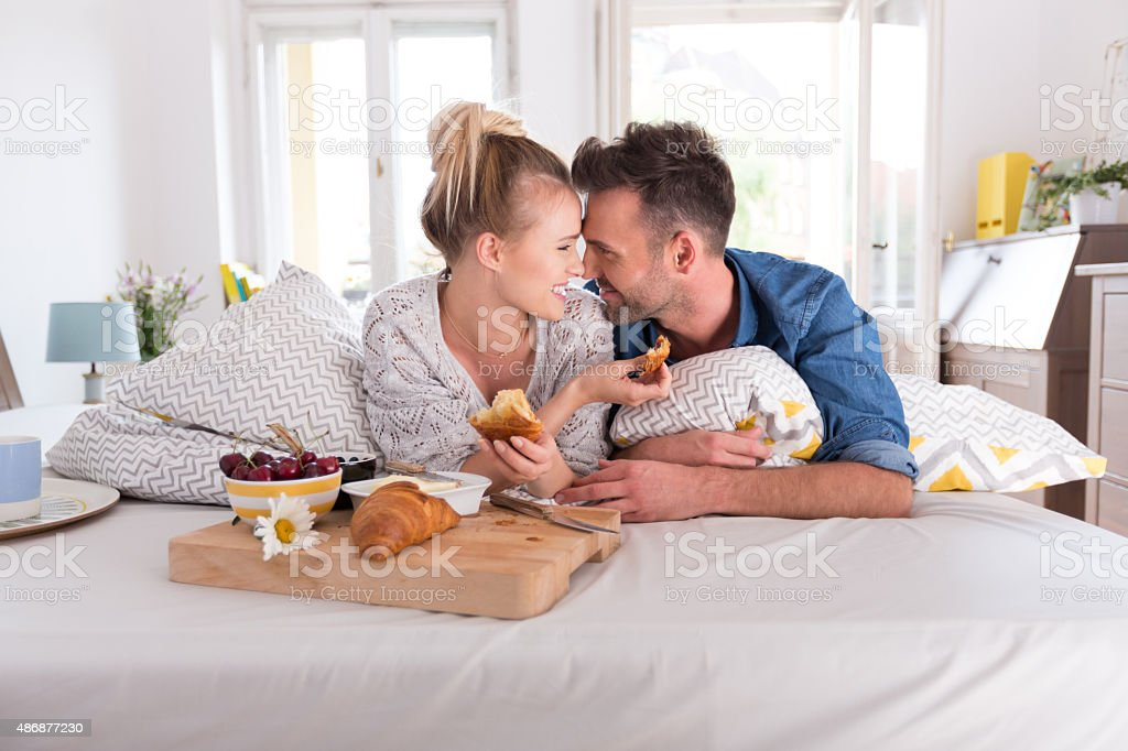 Happy couple eating breakfast in the bed stock photo