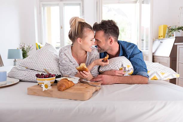 glückliches paar essen frühstück im bett - marvel schlafzimmer stock-fotos und bilder