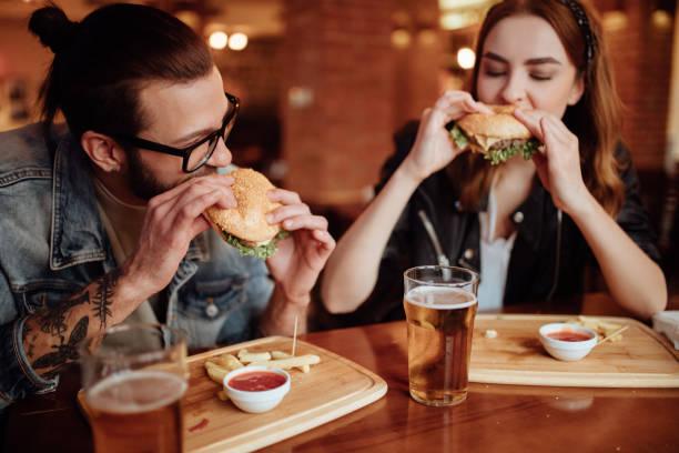 glückliches paar essen burger auf ein rendezvous - essen tattoos stock-fotos und bilder