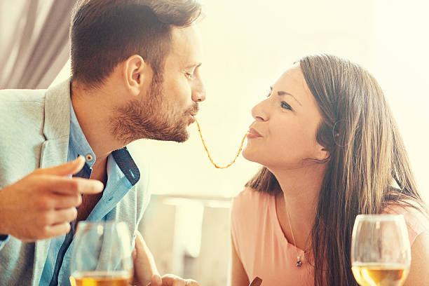 happy couple eating spaghetti - cena romantica fotografías e imágenes de stock
