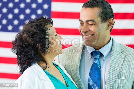 istock Happy couple embrace in front of American flag 539002784
