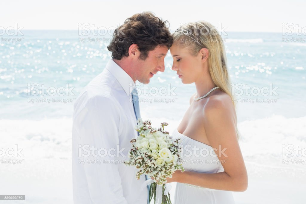 Happy couple embracing each other on their wedding day stock photo