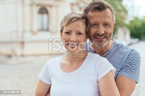 Upper body portrait of middle aged happy couple embracing in city street.