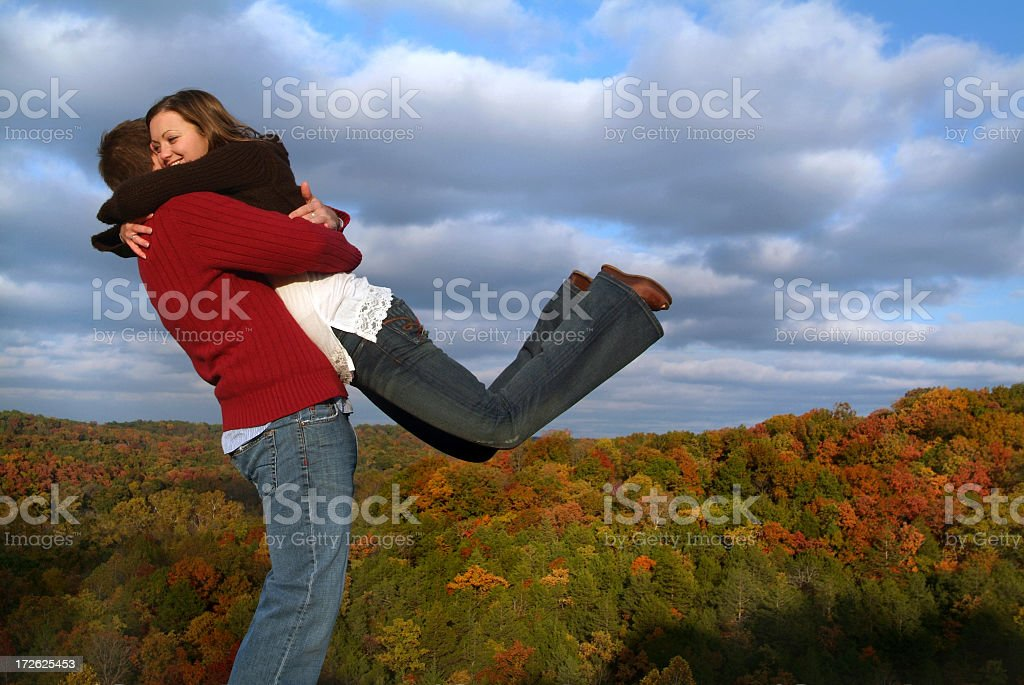 Happy Couple Embracing on a Hilltop in Autumn stock photo