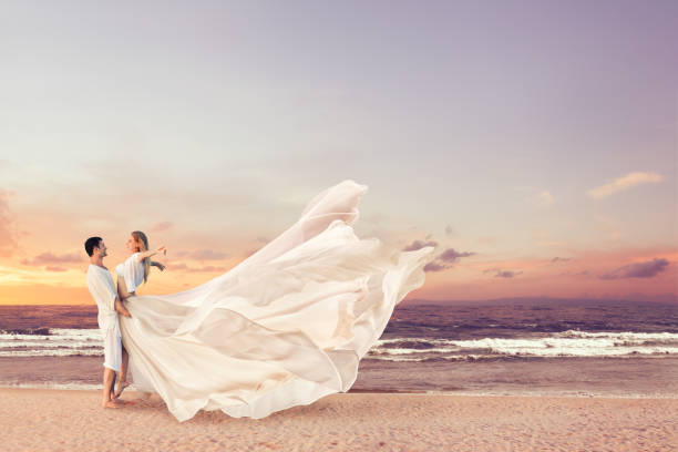 Happy couple embracing on the beach Happy couple embracing on the sea beach. Man holding woman in beautiful long dress on his hands romance stock pictures, royalty-free photos & images