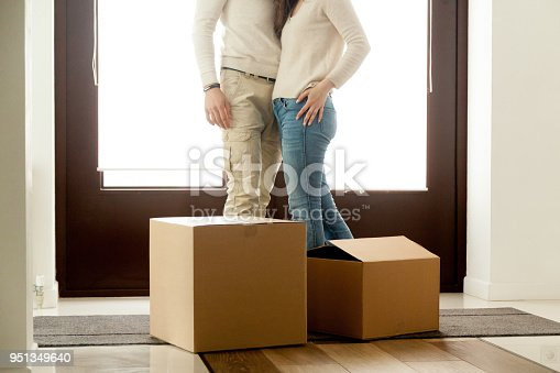 938682826istockphoto Happy couple embracing standing near boxes on moving day, close up 951349640