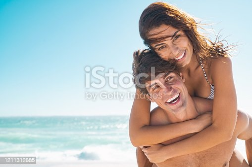 Happy couple in love enjoy summer vacation at beach with copy space. Man giving piggyback ride to his beautiful girlfriend while looking at camera with sea in background. Couple having fun at beach during summer break.