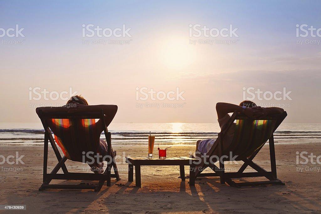 happy couple enjoy sunset on the beach stock photo
