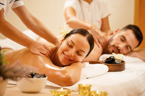 Happy couple enjoying a day at spa while having back massage. Young couple enjoying in back massage at health spa. Focus is on smiling woman. massage stock pictures, royalty-free photos & images