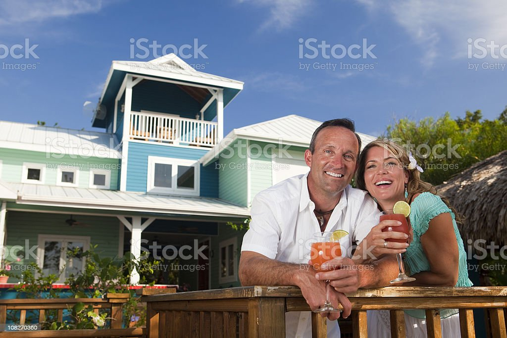 Happy couple enjoying cocktails in front of colorful house royalty-free stock photo