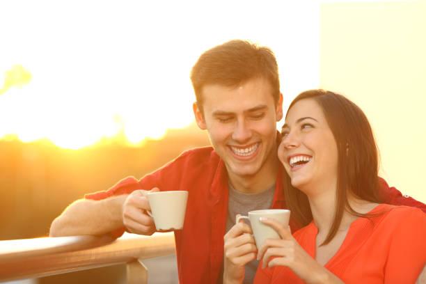feliz pareja disfrutando del café al atardecer en un balcón - happy couple sharing a cup of coffee fotografías e imágenes de stock