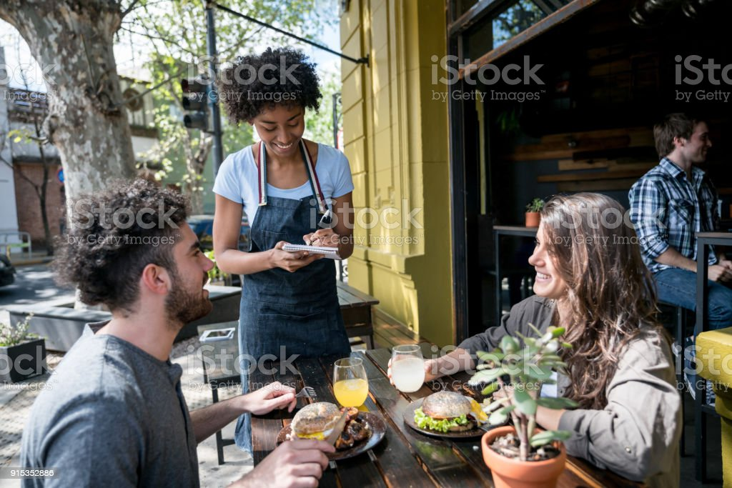 Happy couple enjoying lunch on a lovely day and ordering something to the waitress stock photo