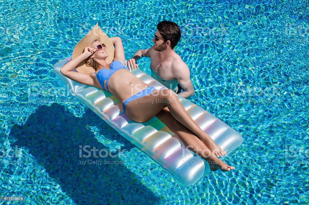 Happy couple enjoying swimming pool stock photo