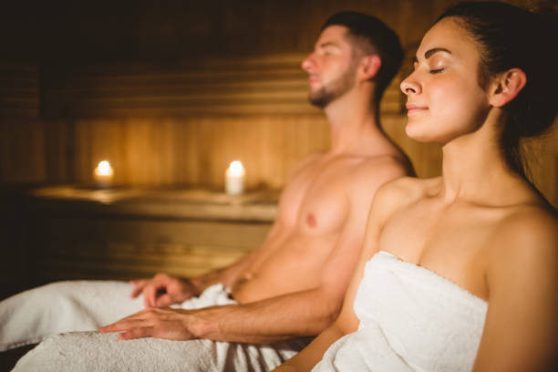 Happy couple enjoying the sauna together Happy couple enjoying the sauna together at the spa sauna stock pictures, royalty-free photos & images