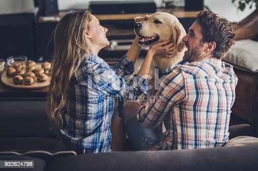 Young happy couple having fun while spending their free time with retriever at home.
