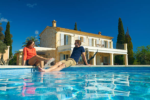 happy couple enjyoing their vacation on spanish finca view from swimming pool at couple sitting in front of finca house on sunny day with clear blue sky holiday villa stock pictures, royalty-free photos & images