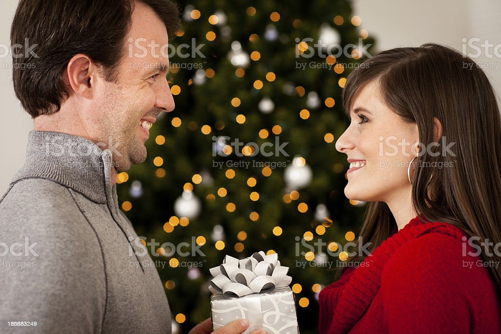 Happy Couple Exchanging Gift with Christmas Tree and Lights royalty-free stock photo