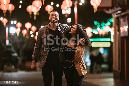 A smiling African American man and woman walk arm in arm on the streets of Chinatown in L.A. California on a warm evening, exploring the cities night life.  Bright traditional lanterns illuminate the scene.