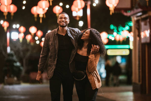 Happy Couple Exploring Chinatown in Downtown Los Angeles At Night A smiling African American man and woman walk arm in arm on the streets of Chinatown in L.A. California on a warm evening, exploring the cities night life.  Bright traditional lanterns illuminate the scene. nightlife stock pictures, royalty-free photos & images