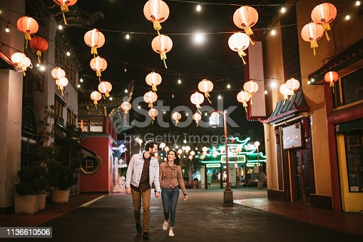 A smiling Caucasian man and woman have fun together on the streets of Chinatown in L.A. California on a warm evening, exploring the cities night life.  Bright traditional lanterns illuminate the scene.