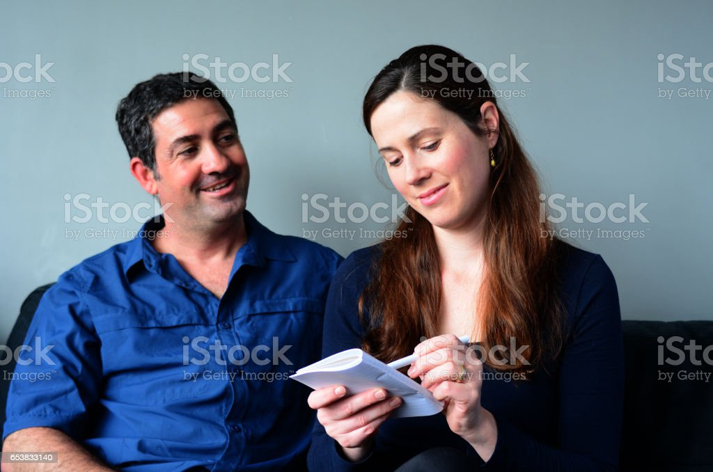 Happy couple filling shopping list stock photo