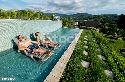 istock Happy couple getting a tan in the swimming pool 815458504