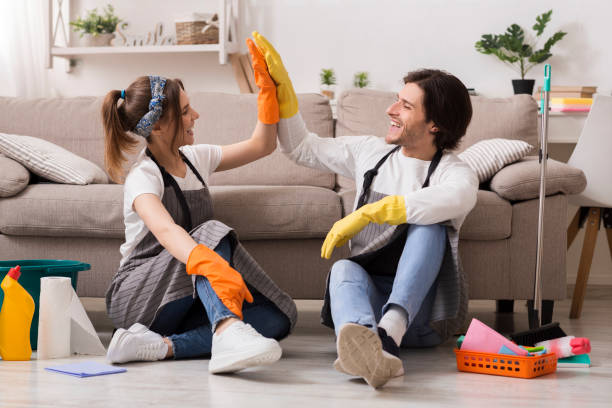 Happy Couple Giving High Five To Each Other After Cleaning Apartment stock photo