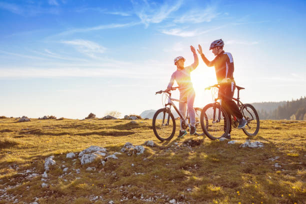 happy couple goes on a mountain asphalt road in the woods on bikes with helmets giving each other a high five happy couple goes on a mountain asphalt road in the woods on bikes with helmets giving each other a high five. female biker resting stock pictures, royalty-free photos & images