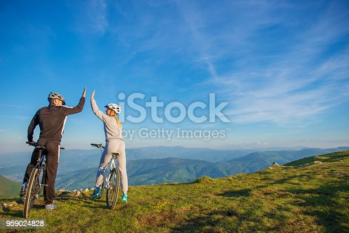 istock happy couple goes on a mountain road in the woods on bikes with helmets giving each other a high five 959024828