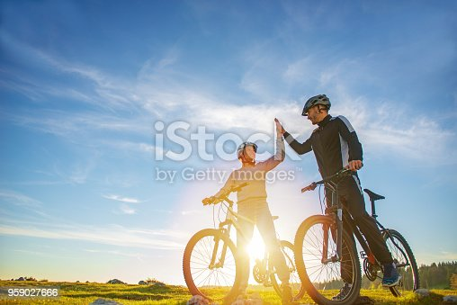 istock happy couple goes on a mountain road in the woods on bikes with helmets giving each other a high five 959027666