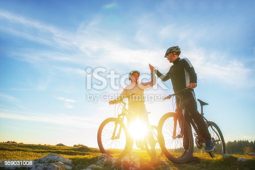 istock happy couple goes on a mountain road in the woods on bikes with helmets giving each other a high five 959031008